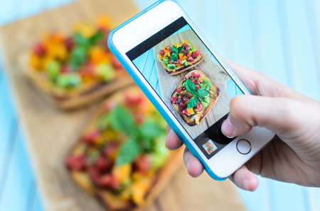 Hands taking photo with smartphone of fresh homemade rustic style bruschetta with chopped red, yellow and green tomatoes, fresh basil and olive oil on toasted garlic italian bread named ciabatta on wooden cutting board over turquoise background, copy spac