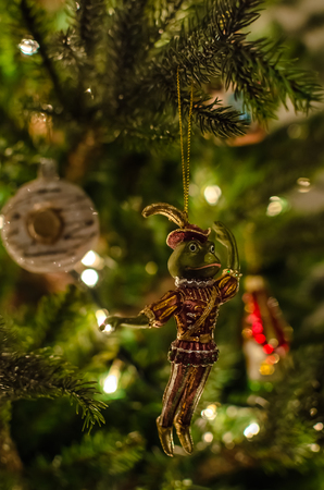 christmas frog: Old fashioned, retro christmas toy of prince of frog on christmas tree close-up with garland lights and beautiful decoration on the background at home indoors on the Christmas or New Years Eve