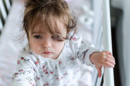 eyes hazel: Portrait of cute little baby girl with black brunette hair in white patterned with flowers long sleeved bodysuit staying in bed at home and looking with curious beautiful hazel brown eyes, top view Stock Photo