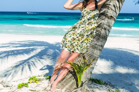 healthy girl: Beautiful, sexy body of young adorable caucasian woman in patterned summer dress staying near palm tree over background of turquoise sea at tropical exotic sandy beach  in the Caribbean sea, Mexico Stock Photo