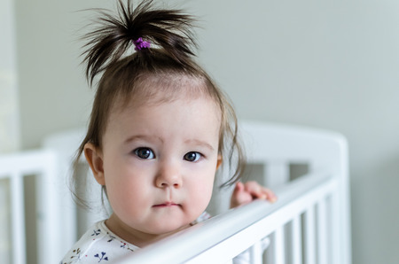eyes hazel: Portrait of cute little baby girl with black brunette hair in white patterned long sleeved bodysuit staying in her bed at home and looking at camera with smart and curious beautiful hazel brown eyes Stock Photo