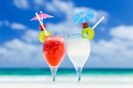 Two fresh cold tasty alcohol Margarita cocktails with lime and strawberry juice, tequila, ice, drinking straw on table against background of turquoise sea on exotic sandy beach in the Caribbean sea
