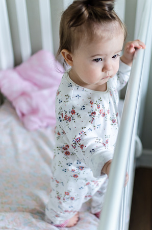 hazel eyes: Portrait of cute little baby girl in full-length with black brunette hair in white patterned long sleeved bodysuit staying in bed at home and looking with smart and curious beautiful hazel brown eyes Stock Photo