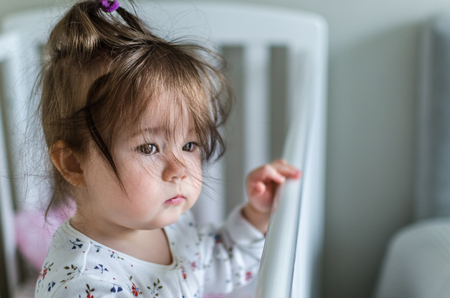 hazel eyes: Portrait of cute little baby girl with black brunette hair in white patterned with flowers long sleeved bodysuit staying in bed at home and looking with smart and curious beautiful hazel brown eyes
