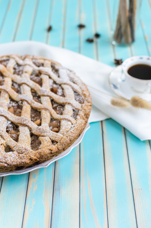 anice: Baked homemade rustic style tart pie with apple jam in ceramic dish next to a cup of coffee, white napkin and cinnamon sticks in a glass jar,star anice on the background over wooden turquoise table close-up, selective focus Stock Photo