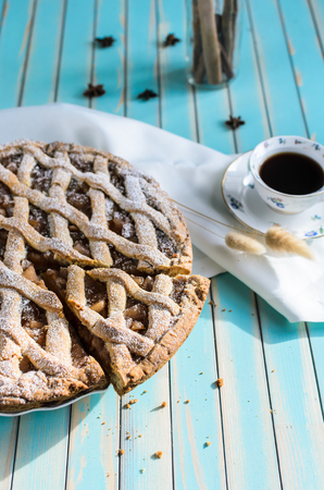 anice: Baked homemade rustic apple tart pie with cutted piece in ceramic dish next to a cup of coffee, white napkin with anice, cinnamon in glass jar on the background over wooden turquoise table, natural side sunlight, selective focus