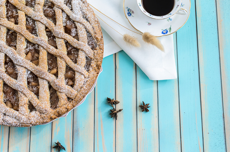 anice: Baked homemade rustic style tart pie with apple jam in ceramic dish next to a cup of coffee, white napkin and star anice over wooden turquoise table background top view, copy space for text