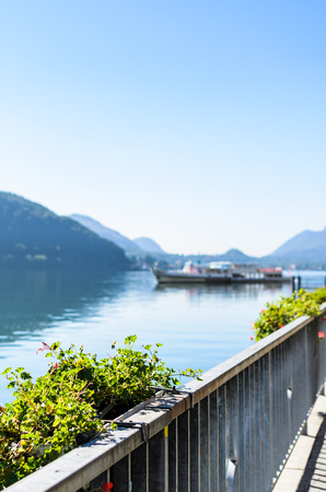 garden scenery: Vacation summer sunny lake view. Beautiful flowers over the background of beautiful serene blue Lugano lake, clear blue sky and a ship surrounded by hills in Morcote, Switzerland, selective focus
