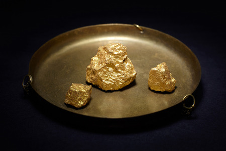 Closeup of big gold nuggets in in copper plate Stock Photo