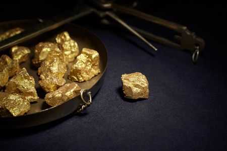 Closeup of big gold nugget and scales copper