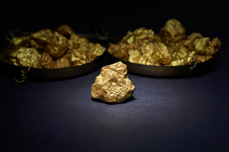 constancy: Closeup of big gold nugget in black background