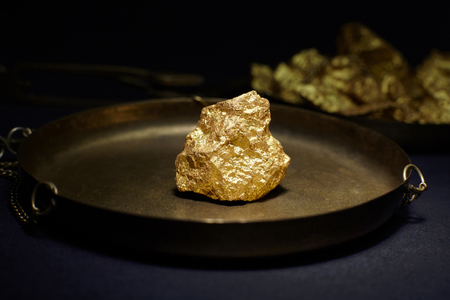 Closeup of big gold nugget in in copper plate