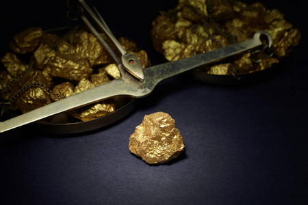 nugget: Closeup of big gold nugget and scales copper