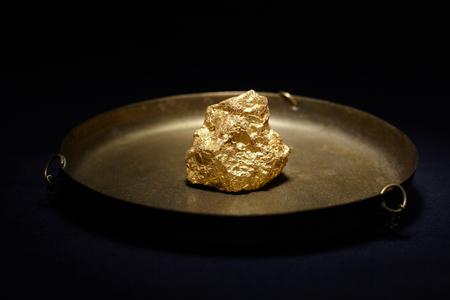 nugget: Closeup of big gold nugget in in copper plate