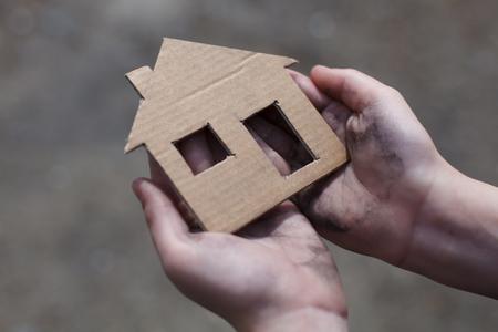 homeless boy holding a cardboard house, dirty hand Stock Photo