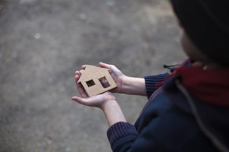 homeless boy holding a cardboard house, dirty hand Stockfoto