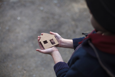 homeless boy holding a cardboard house, dirty hand Foto de archivo