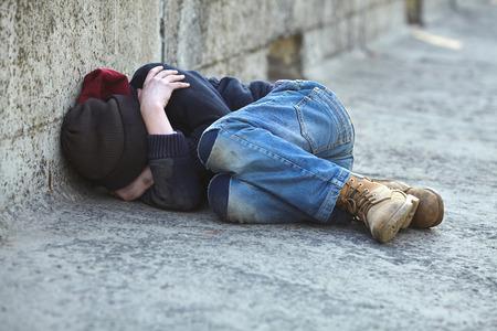 jonge dakloze jongen slaapt op de brug, armoede, stad, straat Stockfoto