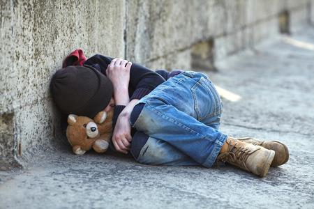 pobreza: muchacho joven sin hogar durmiendo en el puente, la pobreza, ciudad, calle Foto de archivo