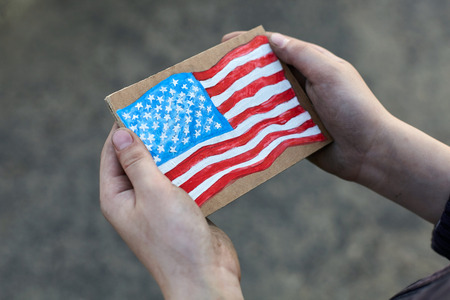 young homeless boy holding a American Flag painted on paper, dirty hand Foto de archivo