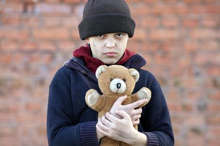 dramatic portrait of a little homeless boy holding a teddy bear Stock Photo