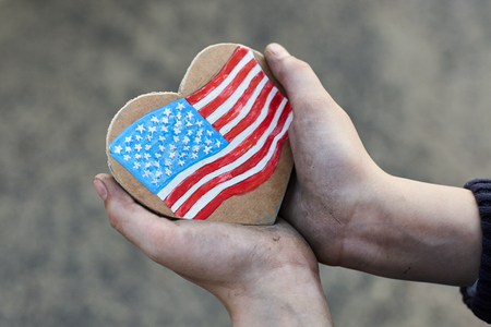 young homeless boy holding a American Heart Flag, dirty hand