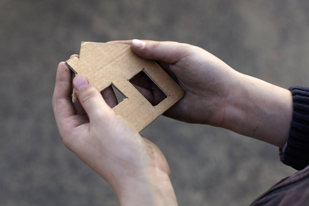 homeless boy holding a cardboard house, dirty hand Stock Photo