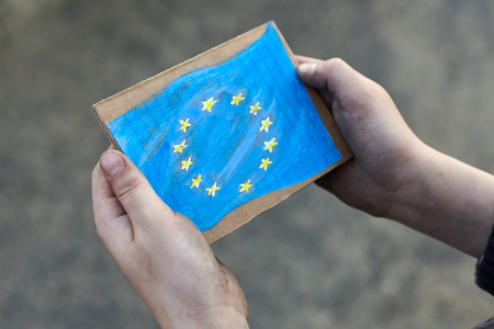 young homeless boy holding European Union flag painted on paper, dirty hand Foto de archivo