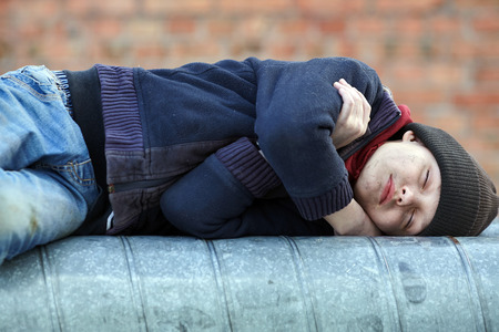 young homeless boy sleeping on a heating pipe, city, street Foto de archivo