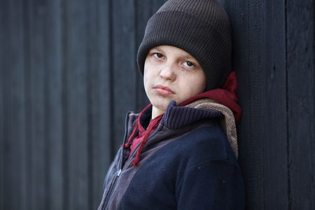 dramatic portrait of a little homeless boy, poverty, city, street, black wall