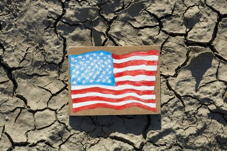 American Flag painted on paper lying on cracked earth, crisis concept Foto de archivo
