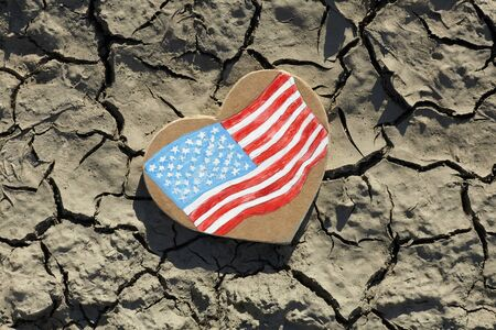 American Heart Flag lying on cracked earth, crisis concept