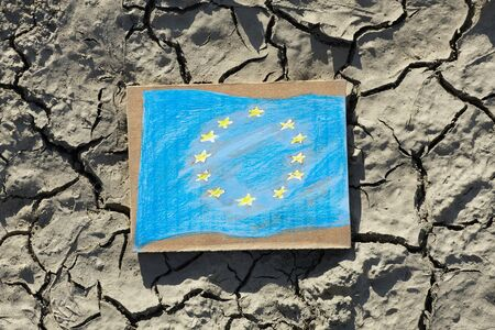 European Union flag painted on paper lying on cracked earth, crisis concept Foto de archivo