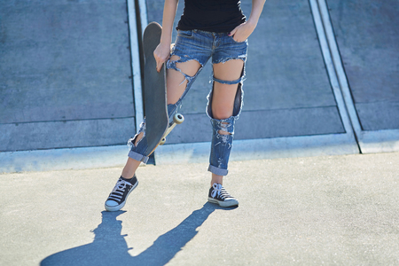 young woman holding a skateboard in torn jeans
