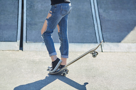 young woman put her foot on a skateboard in torn jeans