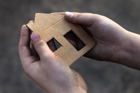 homeless boy holding a cardboard house, dirty hand Imagens