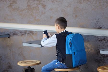 schoolboy using smartphone in cafe, city, street Imagens