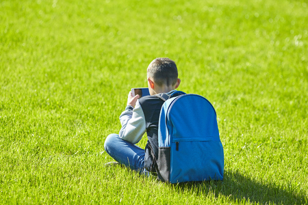 schoolboy using smartphone on a green lawn, school playground 写真素材