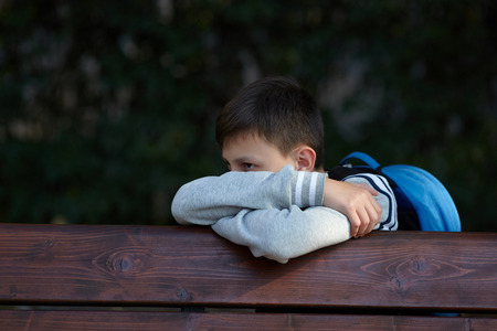 Schoolboy sits on a bench at a school park and cries. Negative emotion.