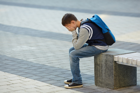 Schoolboy crying in the yard of the school. Negative emotion.