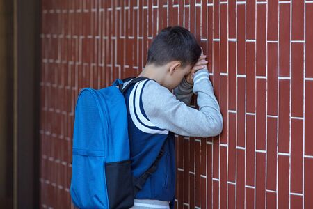 Schoolboy cries in the yard of the school leaning against the wall. Negative emotion.