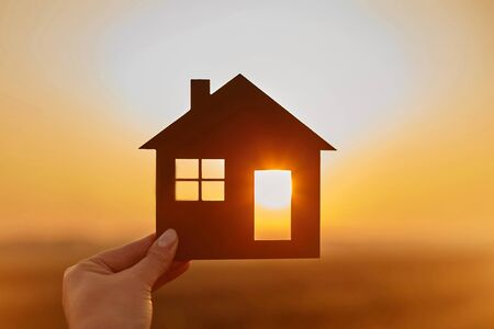Woman hand holds wooden house against the sun. Solar energy. Children dreams. International day of families. Home protection insurance concept. Planning to buy property. A symbol for ecology. Affordable housing. Real estate agent offer house. Choose what's the best. Standard-Bild