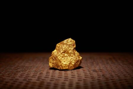 Closeup of big gold nugget. Finance and business concept. Gold ore found in the mine. Trade and exchange.