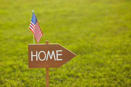 Wooden sign with the inscription Home and American flag. American Independence Day. The concept of patriotism. Real estate concept. Home sweet home.