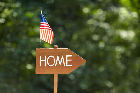 Wooden sign with the inscription Home and American flag. American Independence Day. The concept of patriotism.