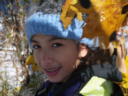 no teeth smile: Close-up of girl with braces wearing winter attire.