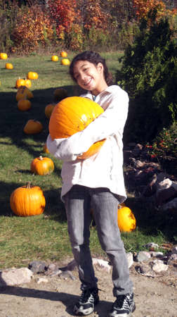 large pumpkin: Mixed race young girl carrying large pumpkin