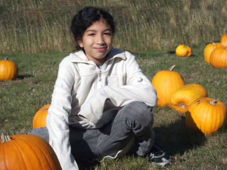 girl squatting: Young mixed race girl squatting in pumpkin patch Stock Photo