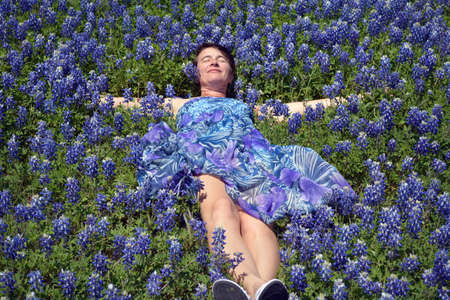 bluebonnet: A women taking a nap in a field of bluebonnet flowers.