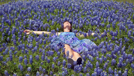 lays down: A women in a beautiful purple dress lays down in a field of bluebonnets Stock Photo